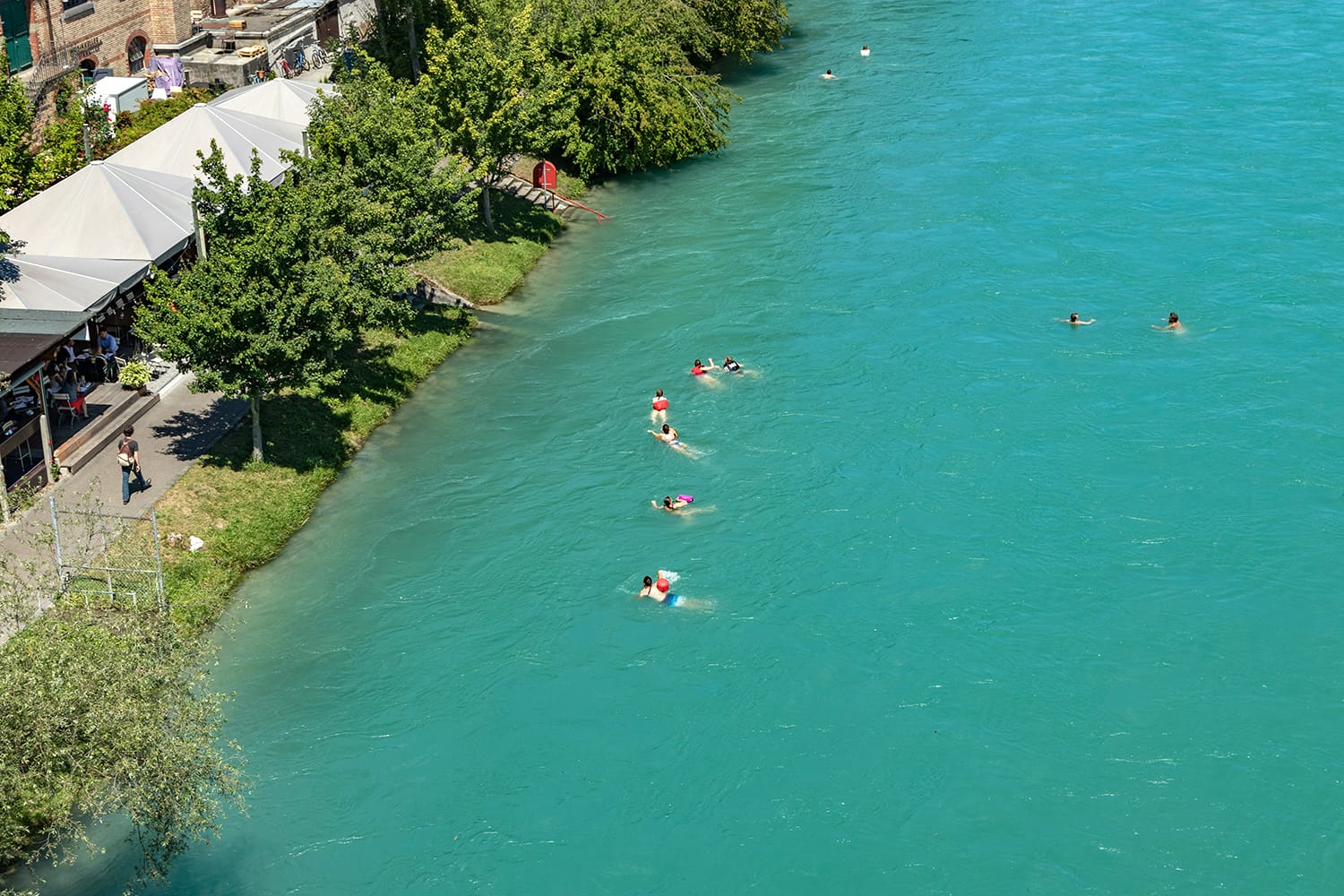 View of Aare river at sunny summer day. Local residents relax, sunbathe and rafting in inflatable boats along the fast flow of the river.