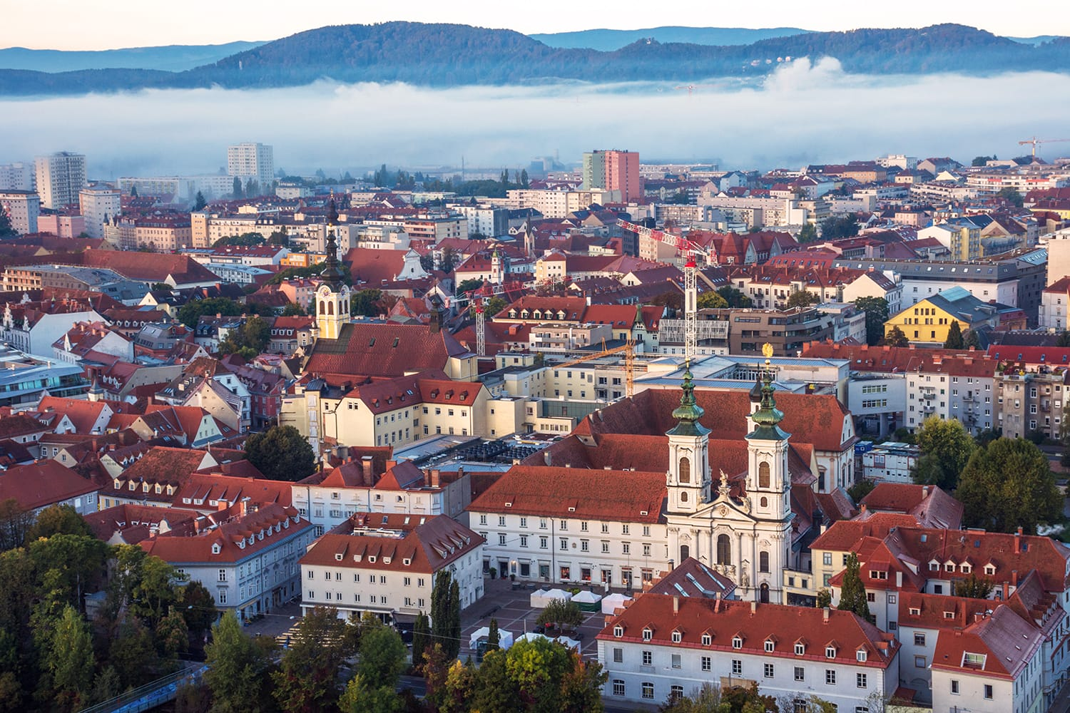 Cityscape of Graz with Mur river and Mariahilfer church (Mariahilferkirche), view from the Shlossberg hill, in Graz, Styria region, Austria