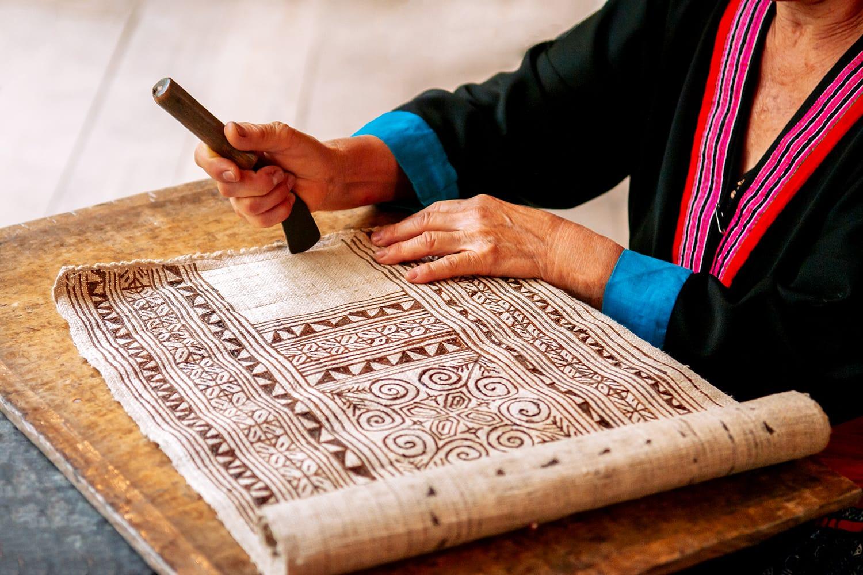 Hilltribe Laotian woman working on Batik fabric painting. Culture tourism at Ock Pop Tok handicraft center, Luang Prabang, Laos