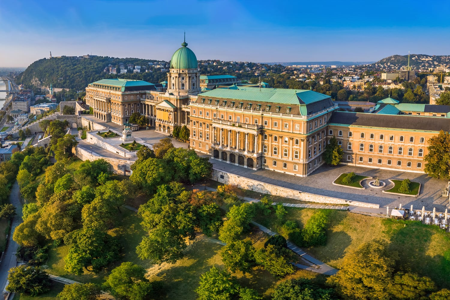 Aerial panoramic view of the beautiful Buda Castle Royal Palace at sunrise with Gellert Hill and Statue of Liberty at background