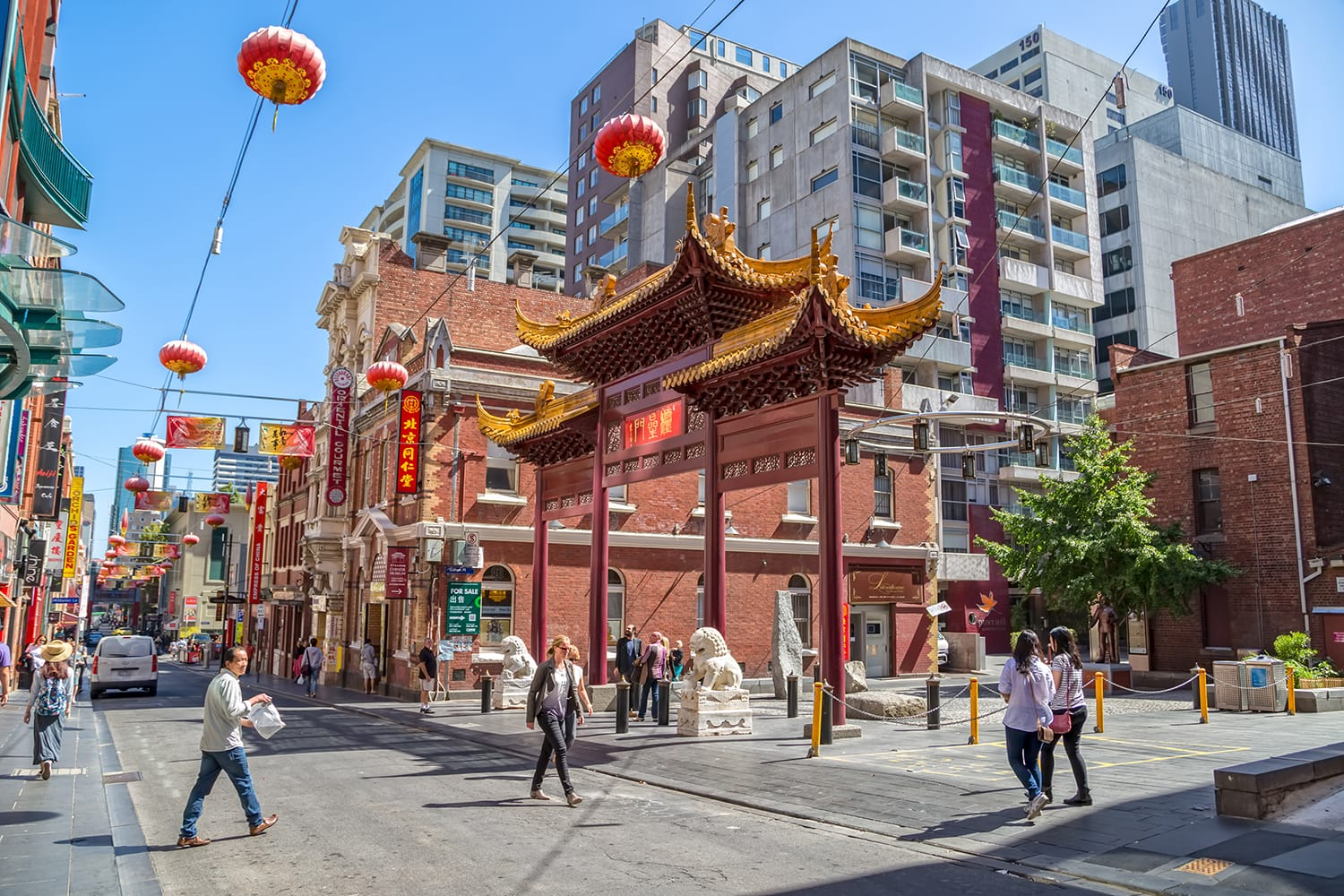 People walk down the Chinatown main street by the Heaven archway, gift from Jiangsu province. Melbourne, Australia