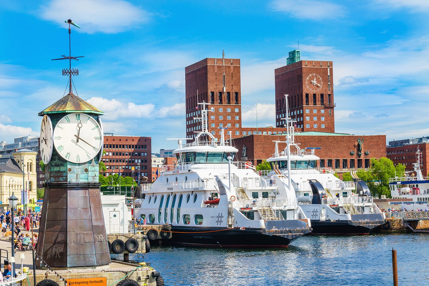 Clock on Aker Brygge Dock, modern and very popular part of Oslo in the background of the famous Oslo City Hall and the harbor, Oslo Fjord, Norway, Scandinavia