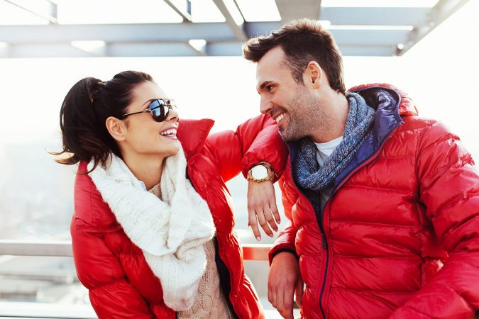 Happy couple enjoying time together at winter time wearing down jacket