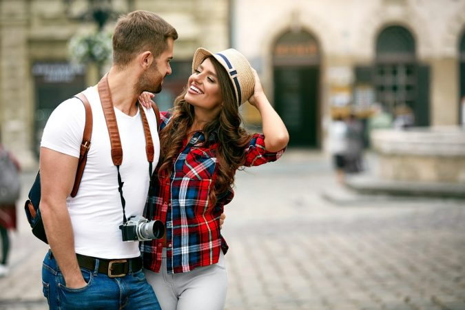 Beautiful Tourist Couple In Love Walking On Street Together. Happy Young Man And Smiling Woman Walking Around Old Town Streets, Looking At Architecture. Travel Concept.
