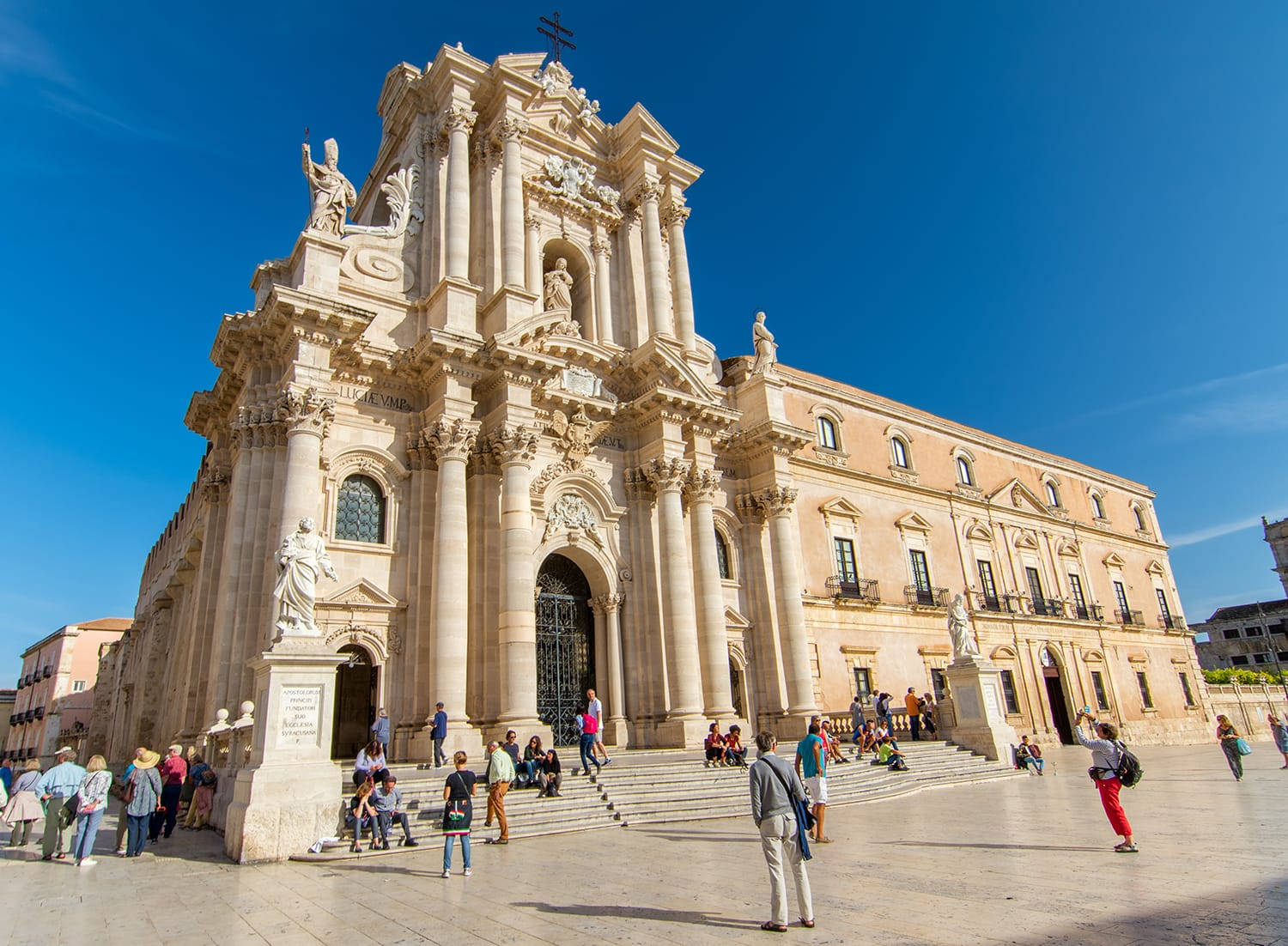 Tourists visiting Duomo Square in Ortigia, the historical city centre of Syracuse, Italy