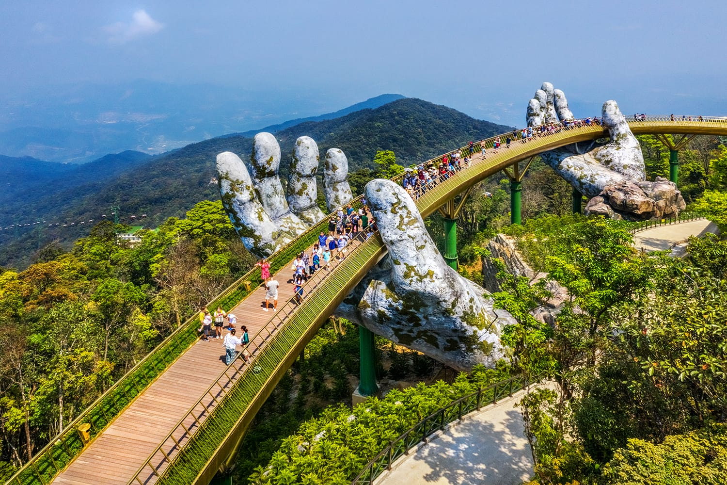 Aerial view of the Golden Bridge is lifted by two giant hands in the tourist resort on Ba Na Hill in Da Nang, Vietnam