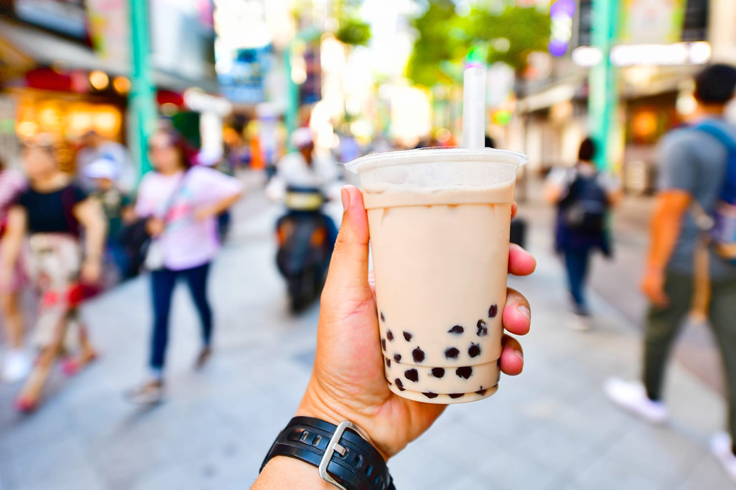 Hand holding a plastic glass of Taiwan iced bubble milk tea on crowded street background