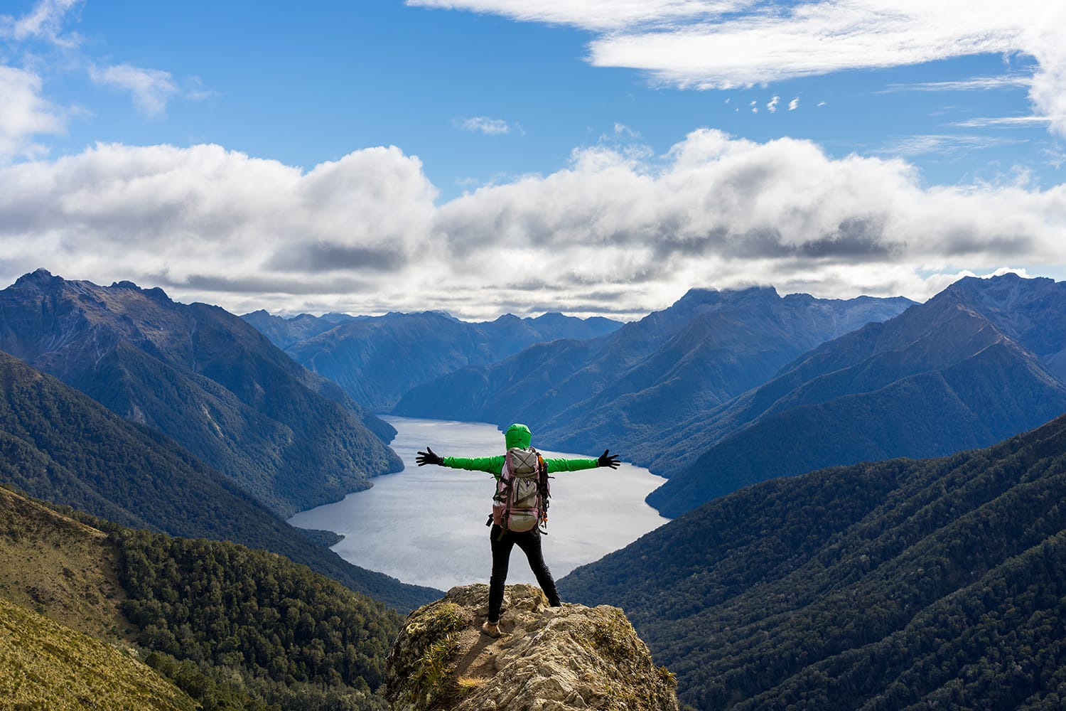 Woman hiker on mountain cliff. Kepler Track, New Zealand