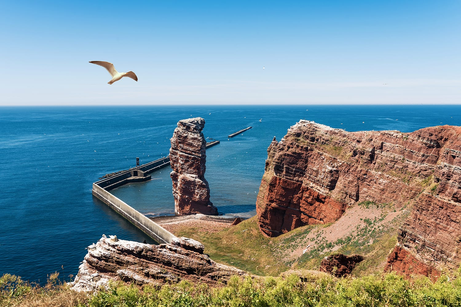 high angle view of Lange Anna sea stack rock on Heligoland island against blue sea and clear sky