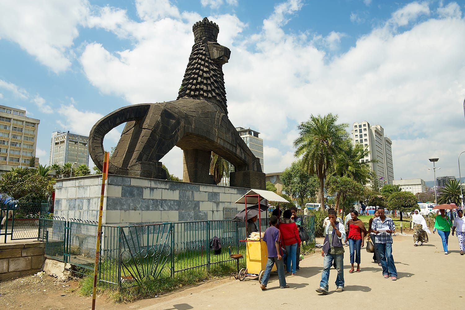 Unidentified people walk by the street next to the iconic statue of the Lion of Judah in Addis Ababa, Ethiopia.