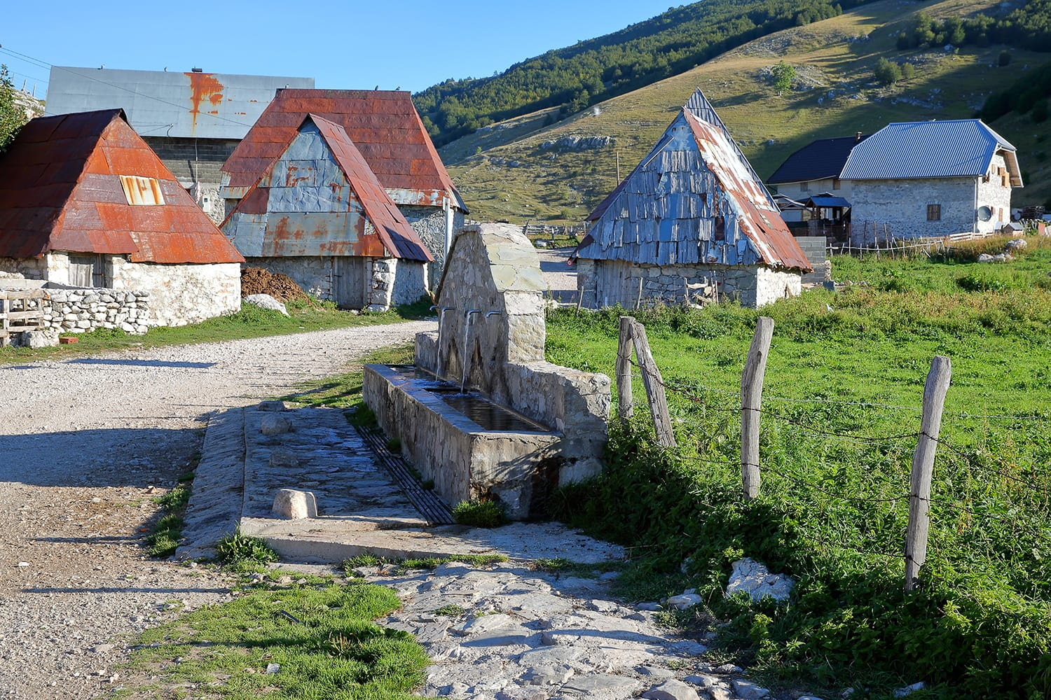 Traditional houses in Lukomir village, with a fountain in the foreground. Lukomir is Bosnia's highest village at 1469 meters and the most remote in the entire country, Bosnia and Herzegovina