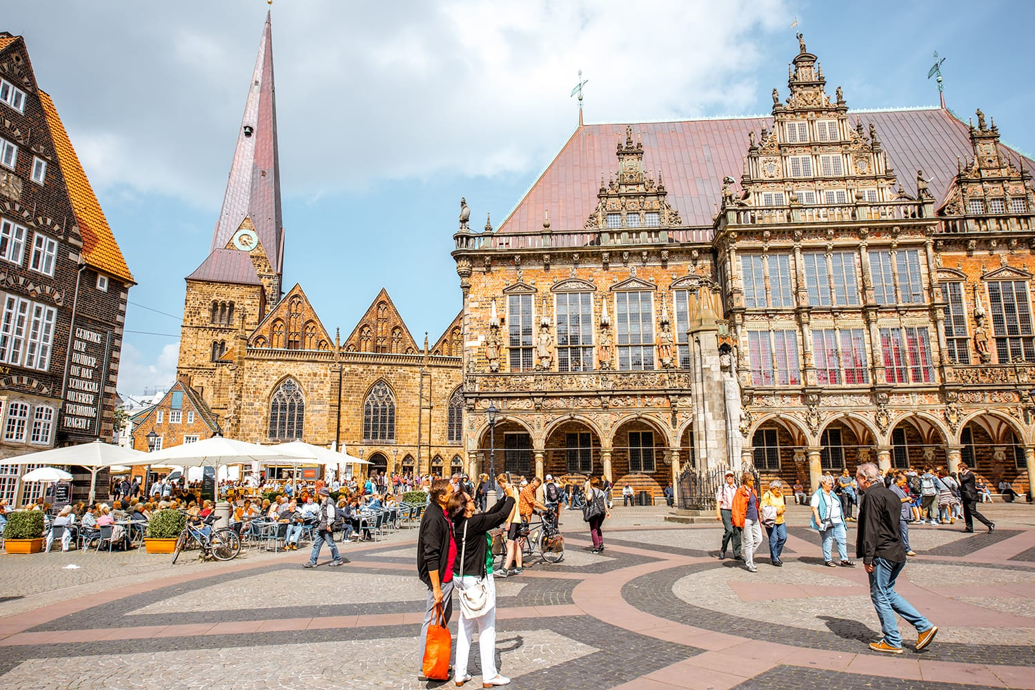 View on the Market square full of tourists with beautiful city hall building during the sunny weather in Bremen, Germany