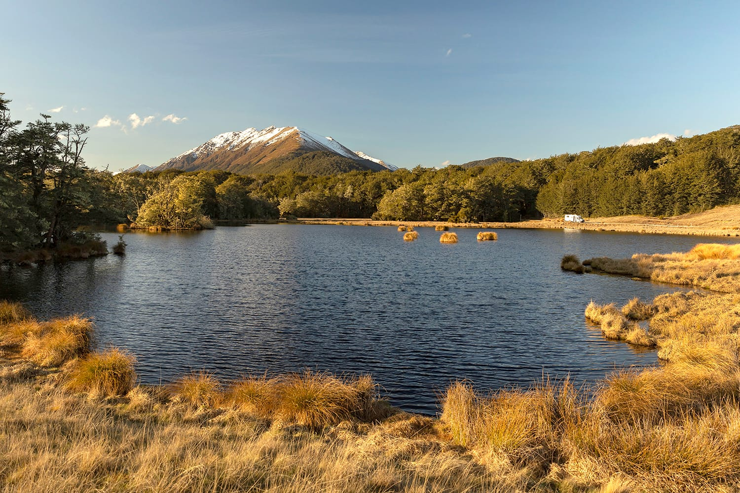 Little Mavora Lake in the south of the South Island of New Zealand with a white motorhome on the far shore with mountains in the background