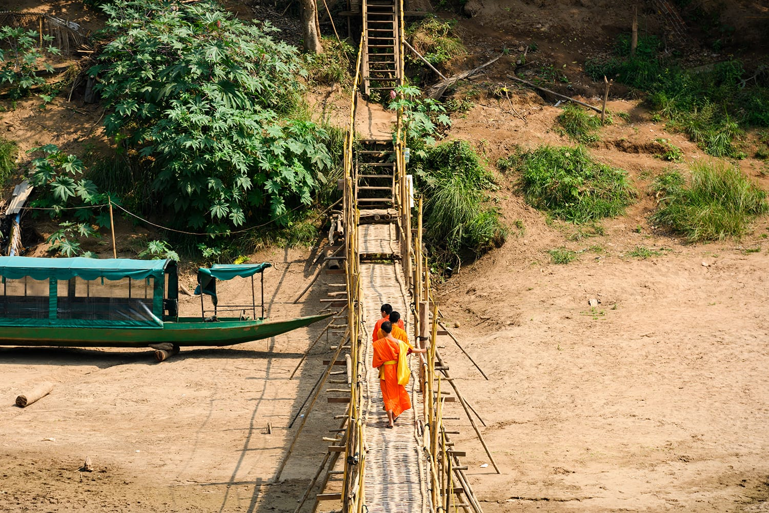 Three unidentified Buddhist monks are crossing the Bamboo Bridge that run across the Nam Khan river. The Bamboo Bridge is hand made out of bamboo and is one of the tourists attractions in Luang Prabang, Laos.