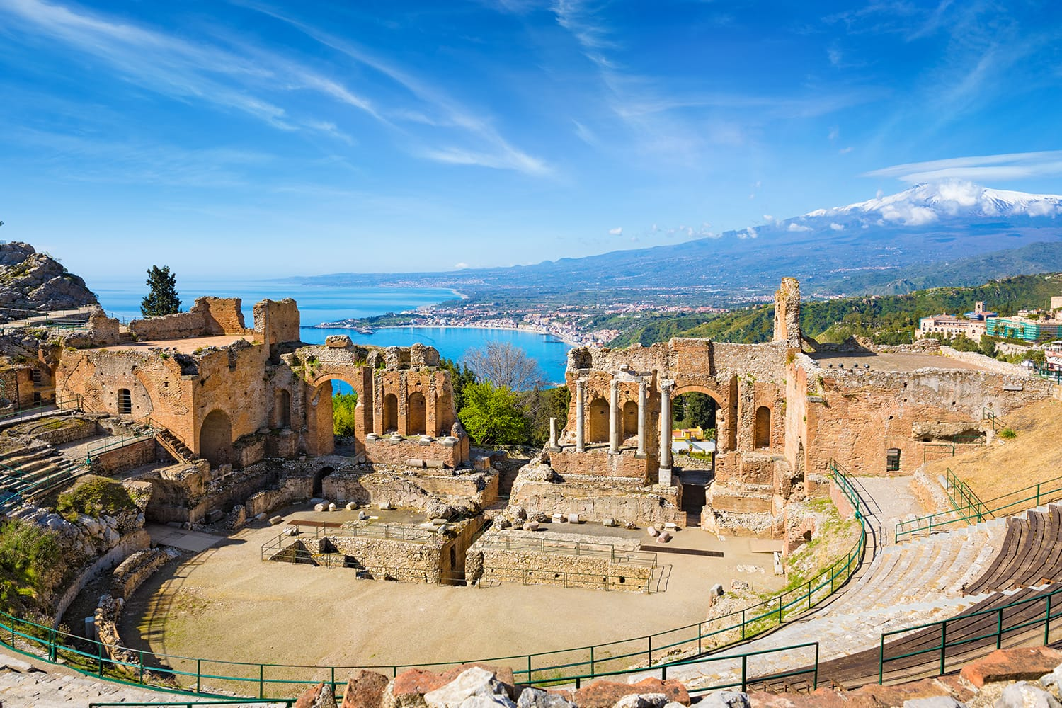 Ruins of Ancient Greek theatre in Taormina on background of Etna Volcano, Italy