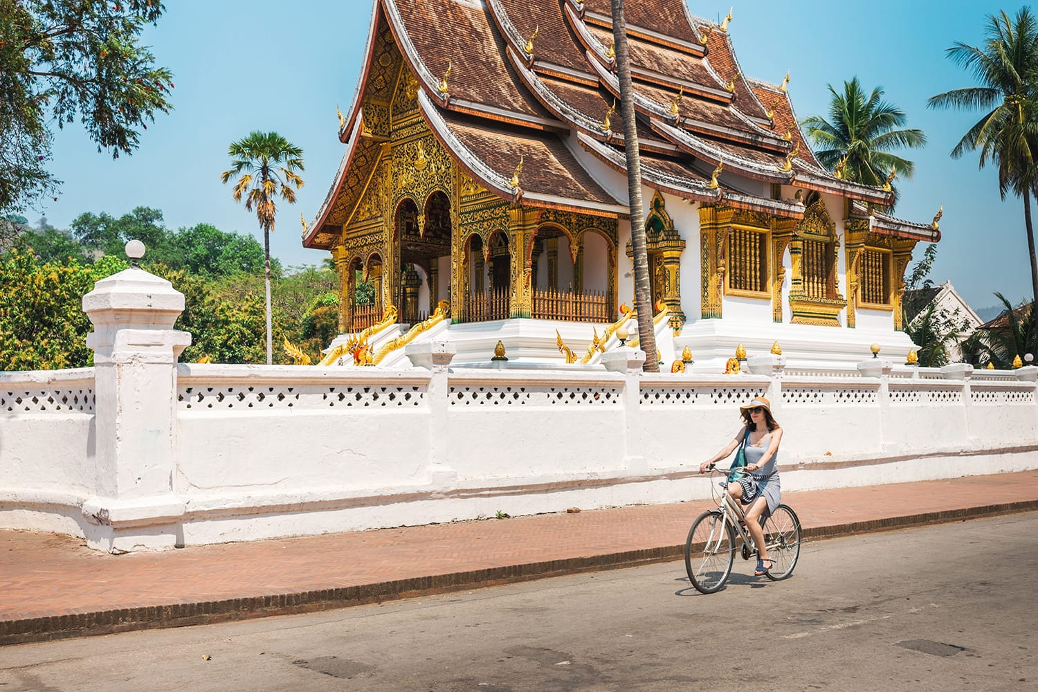 Girl tourist riding a bicycle in Luang Prabang against the backdrop of a traditional temple.A popular way among tourists is to visit Luang Prabang in Laos - a bicycle.