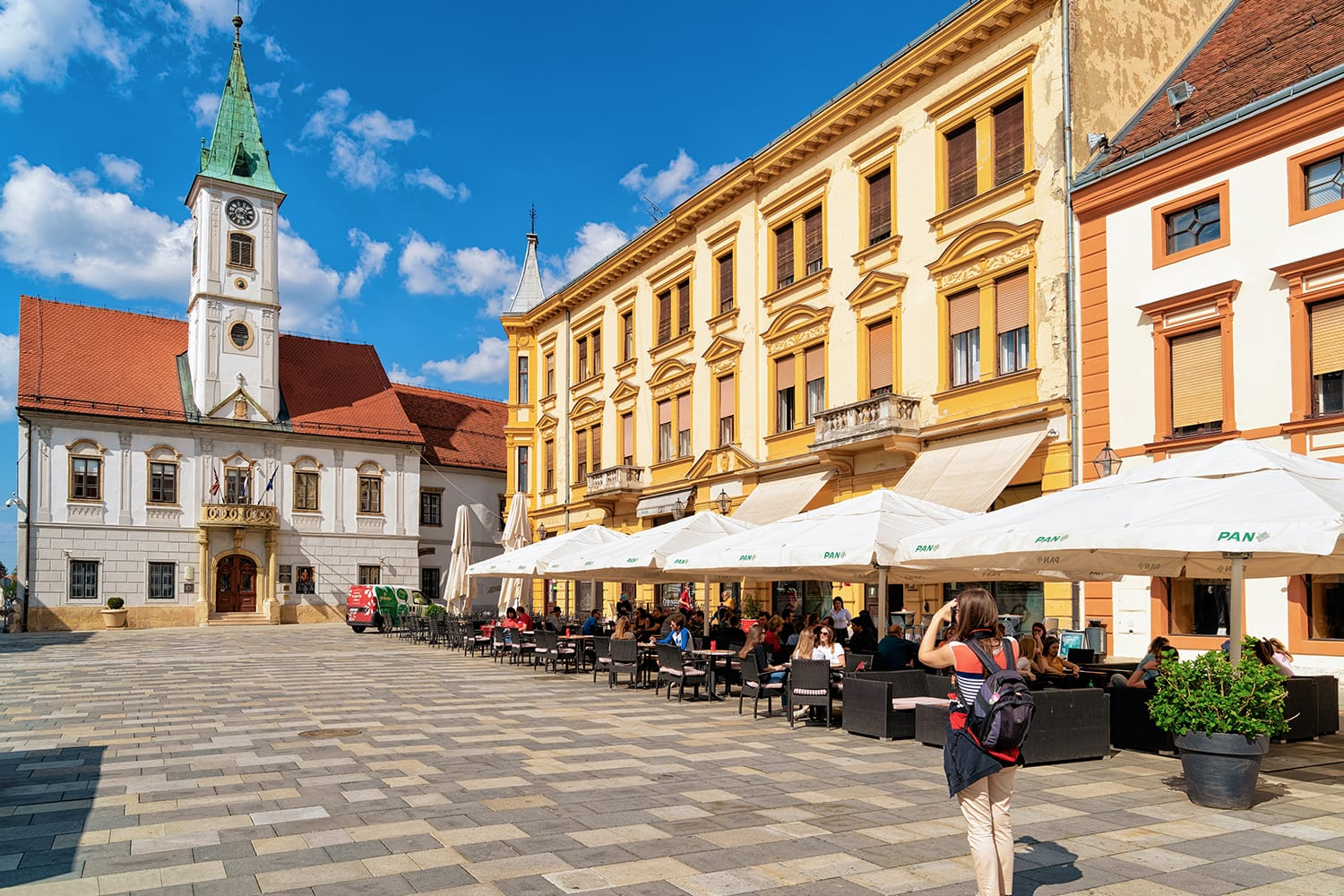 Girl photographer taking photos at Street cafes and restaurants at Town Hall on King Tomislav Square in Old city of Varazdin in Croatia