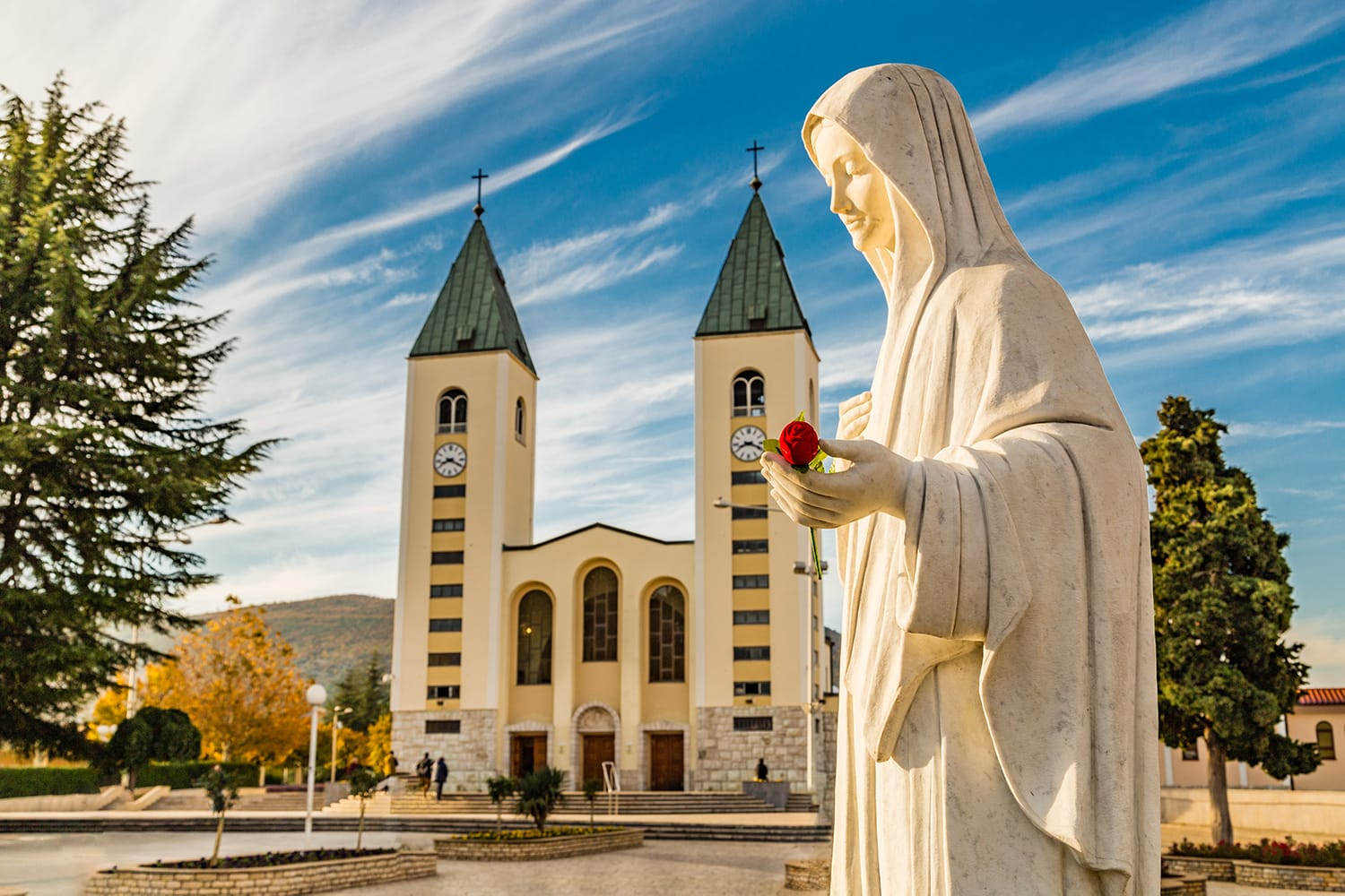 statue of the Blessed Virgin Mary holding a red rose while Saint James Church in Medjugorje, Bosnia & Herzegovina