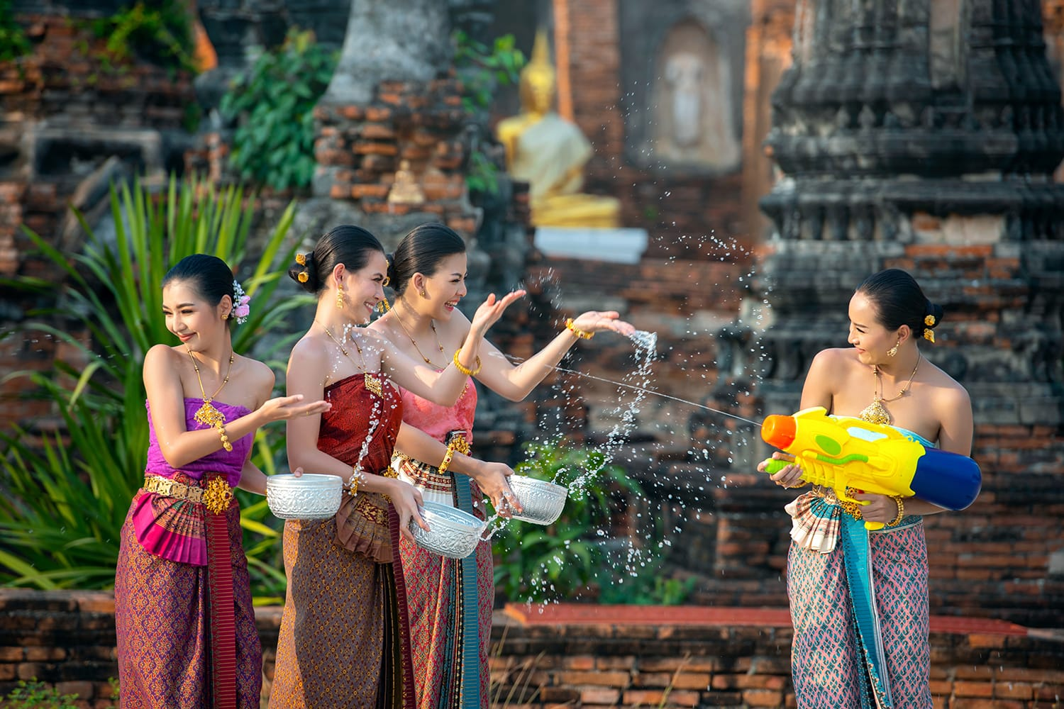 Water Songkran festival. Asia young woman wearing Thai traditional costume play water in Songkran day water festival of Thailand. Women group using water gun and bolw play in the temple.