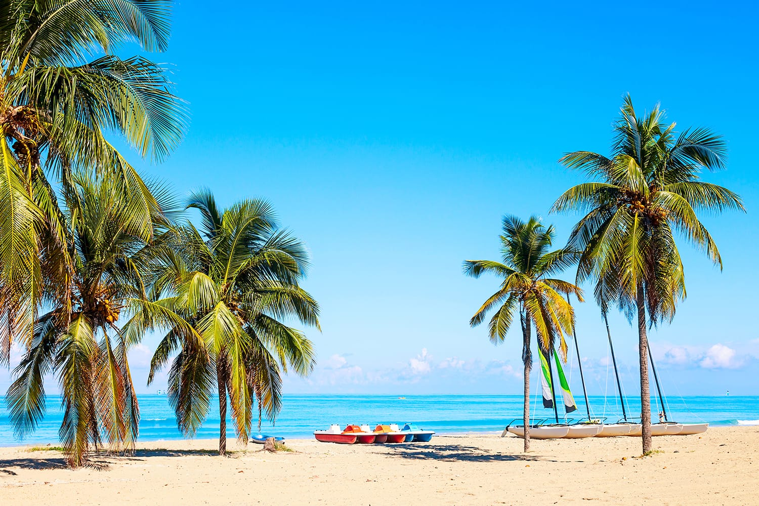 The tropical beach of Varadero in Cuba with sailboats and palm trees on a summer day with turquoise water.