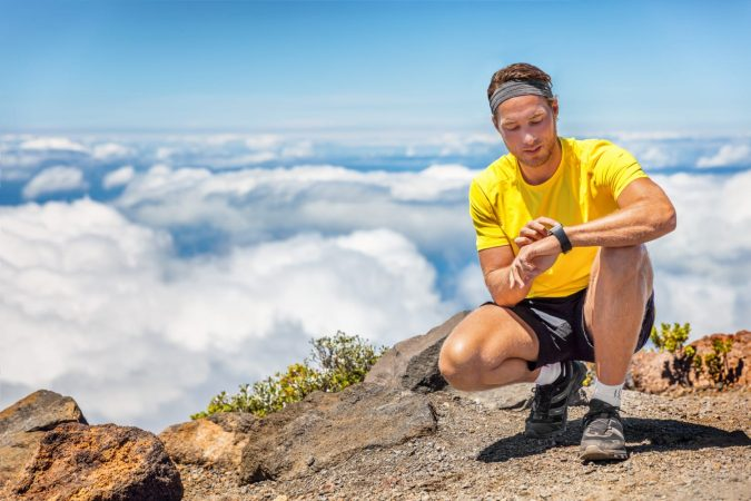 Sport man touching smartwatch on mountain hike trail running summer outdoors sports lifestyle. Athlete fitness runner getting ready to run in mountains.