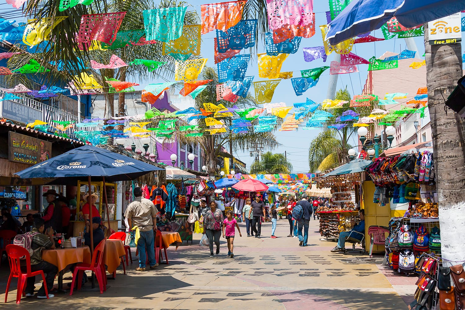 People shop and walk below colorful hanging flags at Plaza Santa Cecilia, a historic Mexican square in the heart of Tijuana, Mexico
