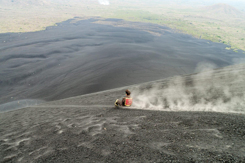 Tourist is volcano boarding from Cerro Negro volcano, Nicaragua