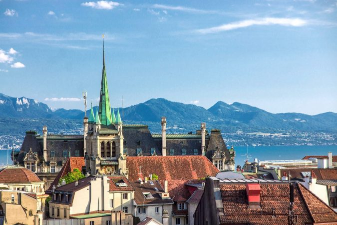 View of the Swiss city of Lausanne on Lake Geneva and the Alps