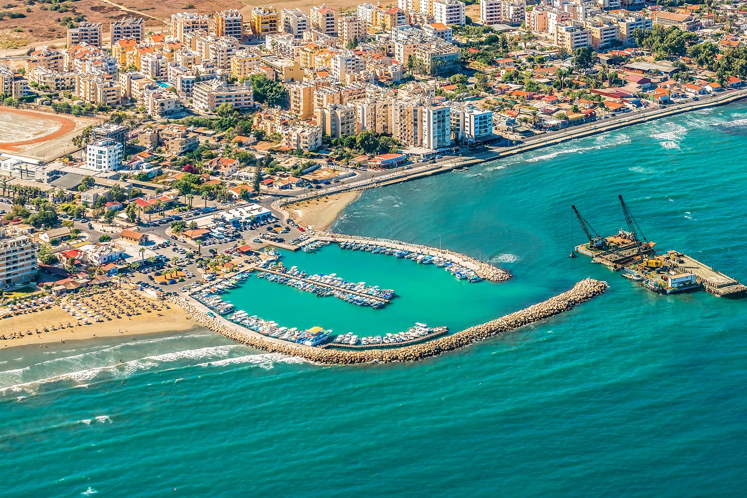 Sea port city of Larnaca, Cyprus. View from the aircraft to the coastline, beaches, seaport and the architecture of the city of Larnaca.