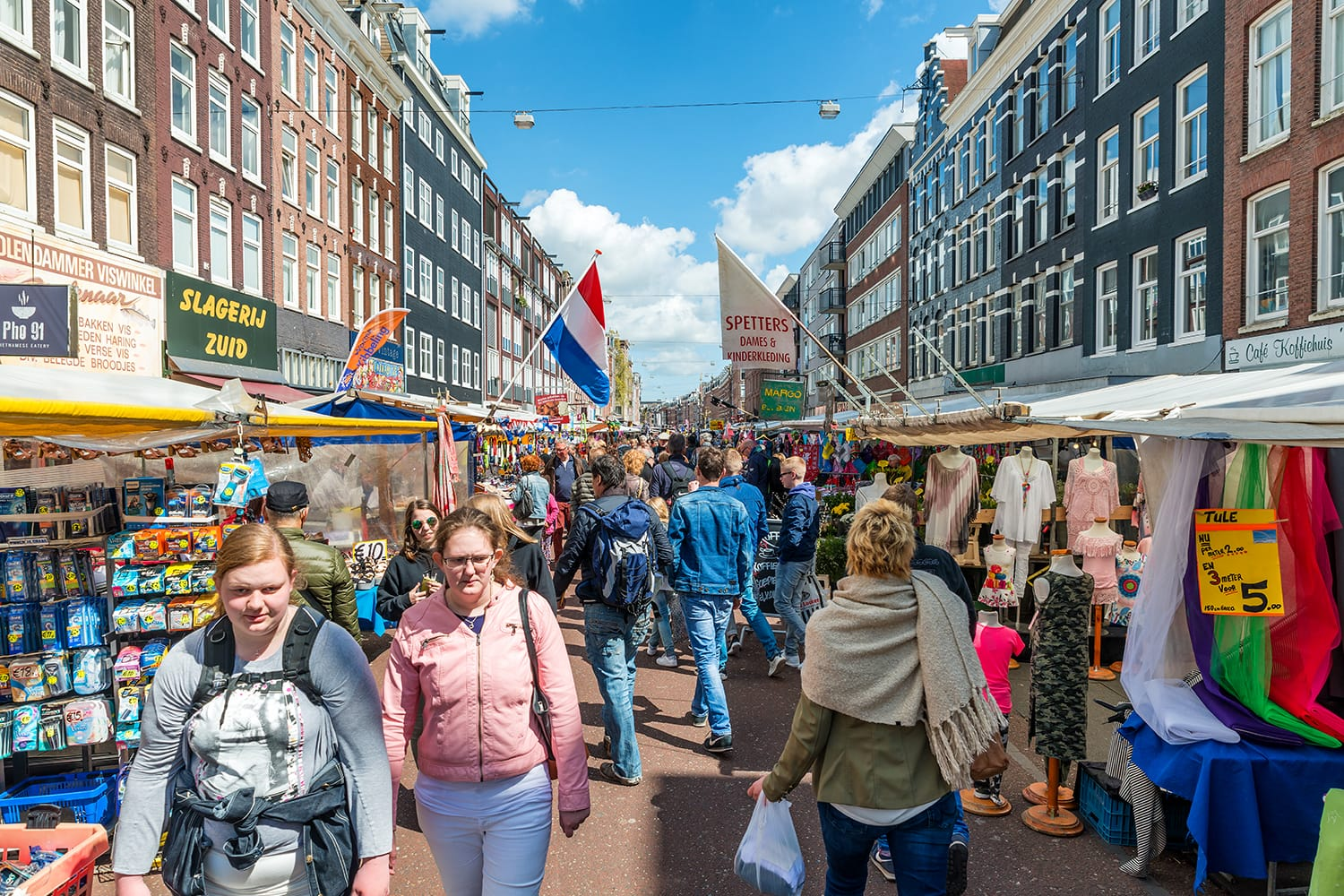 Tourists walk in Albert Cuyp Market. Albert Cuyp Market is one of sights of the city in Amsterdam, Netherlands