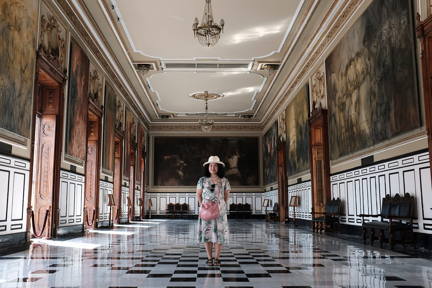 An Asian female tourist is posing for a picture inside the main hall of Government Palace - Palacio del Gobierno in Main Square, Merida, Yucatan, Mexico.