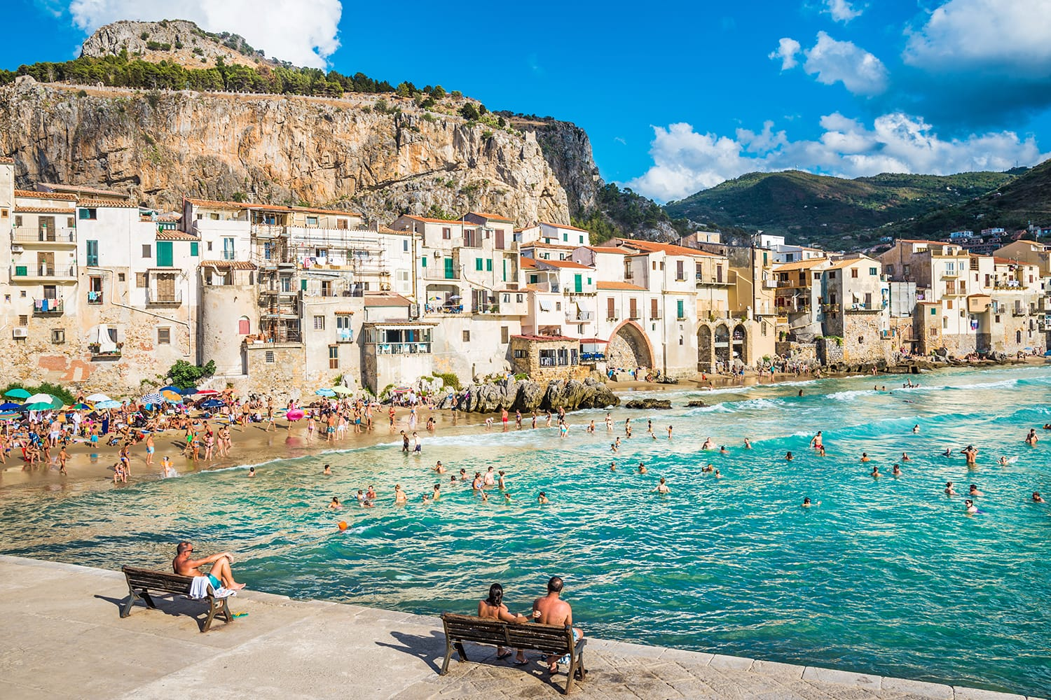 People on beautiful beach at the bay in Cefalu, Sicily