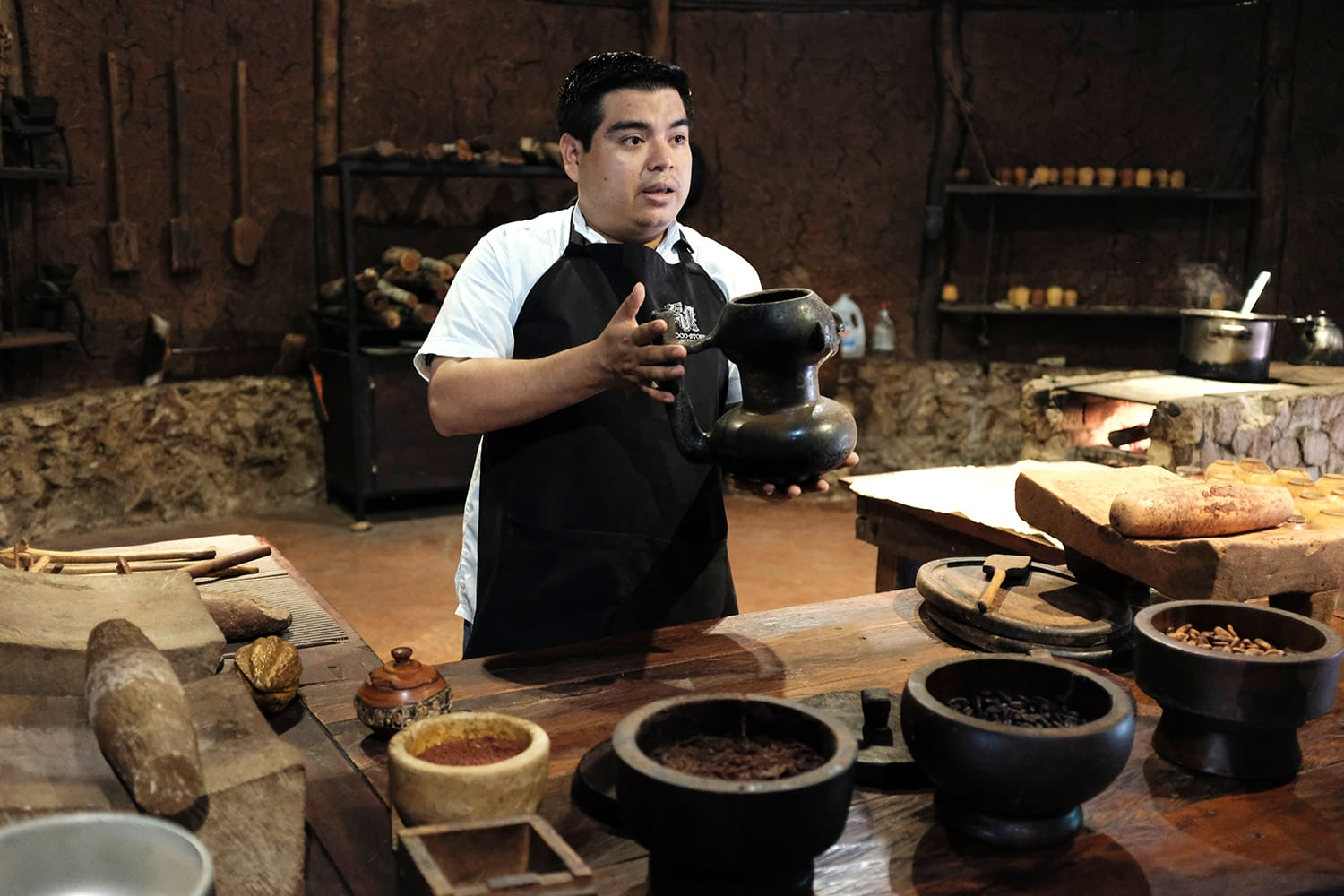 A local Mexican staff at the Chocolate museum explaining the process of how to make a Mayan chocolate drink from cocoa beans.