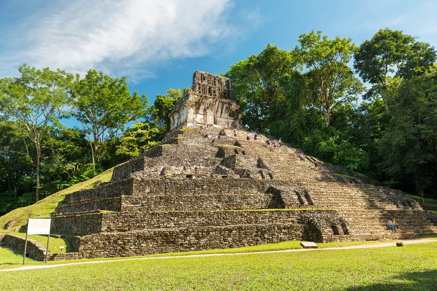 Unknown people explore the mayan temple ruins surrounded by dense jungle in Palenque Mexico