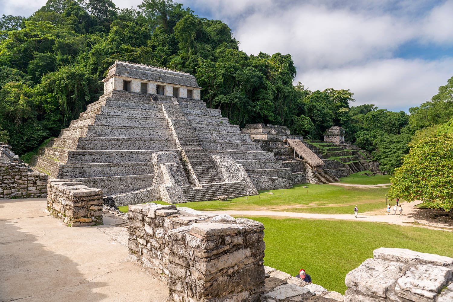 Unidentified people in the mayan temple ruins surrounded by dense jungle in Palenque Mexico