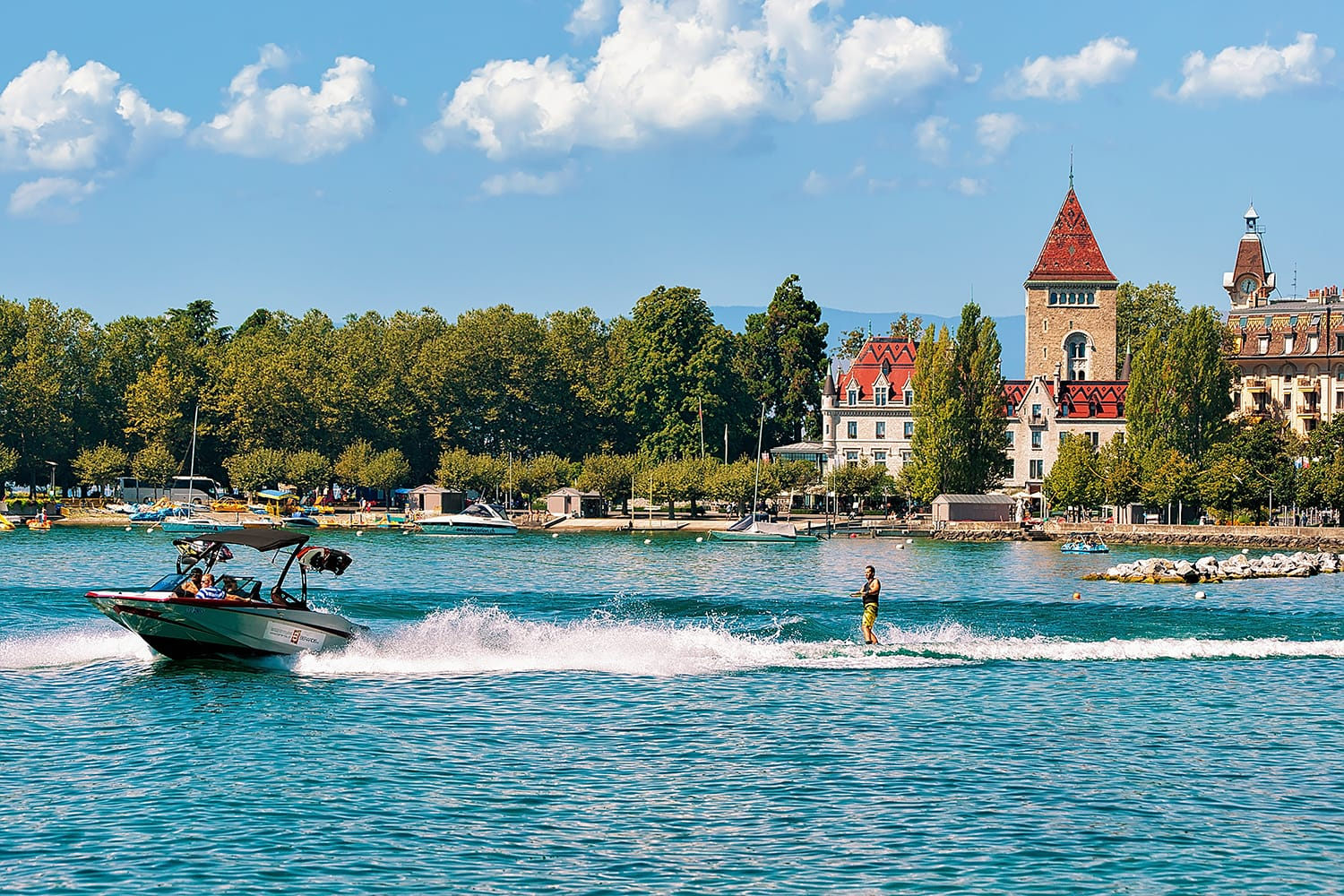 Motorboat with man wakeboarding on Lake Geneva embankment near Chateau Ouchy in Lausanne, Switzerland.