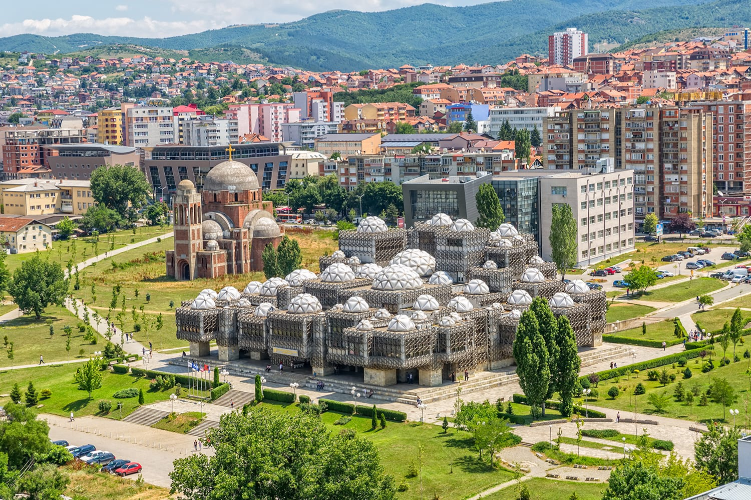Aerial view of capital city with some old buildings like National Public Library and Christ the Saviour Cathedral. Pristina, Kosovo