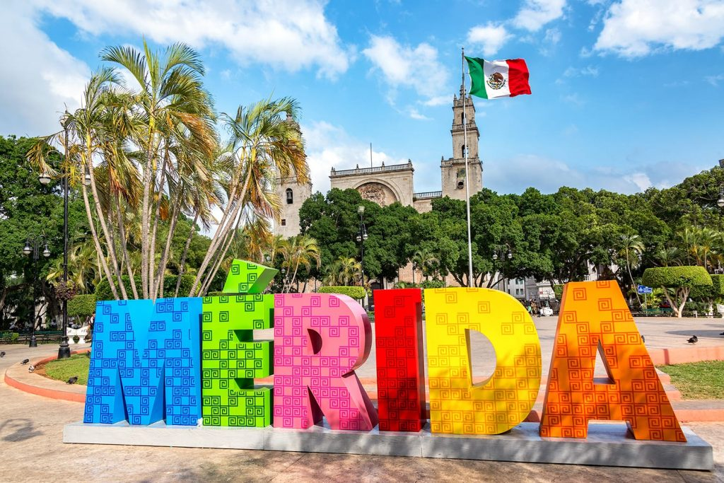 Colorful Merida sign with a Mexican flag and cathedral in the background in Merida, Mexico