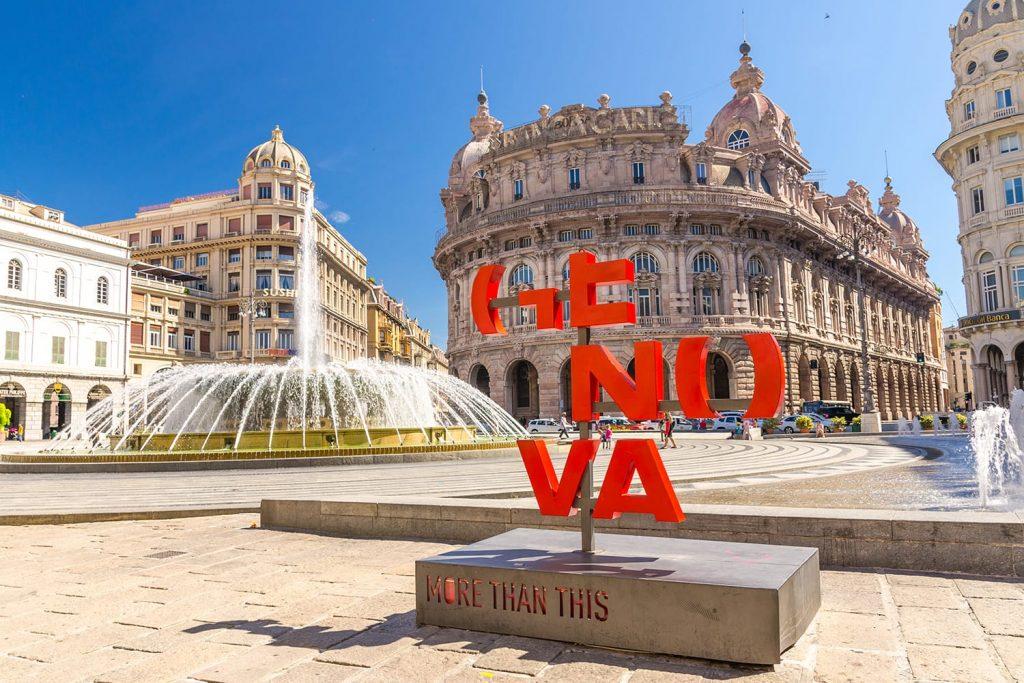 Red letters Genova More than this catchphrase on Piazza De Ferrari square, fountain and Palazzo della Nuova Borsa Palace barocco style in historical centre, Liguria