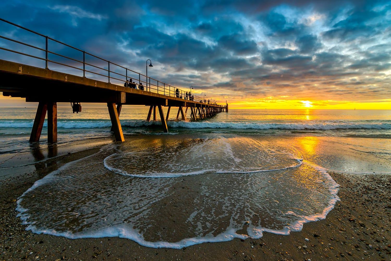 People walking along Glenelg Beach jetty at sunset, South Australia