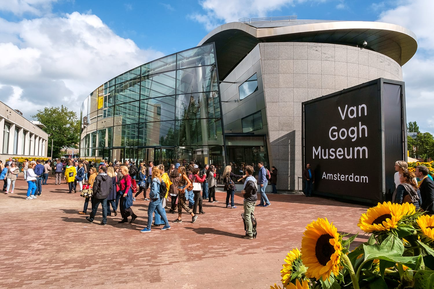crowd in front of the new wing of the Van Gogh Museum with sunflowers in the foreground