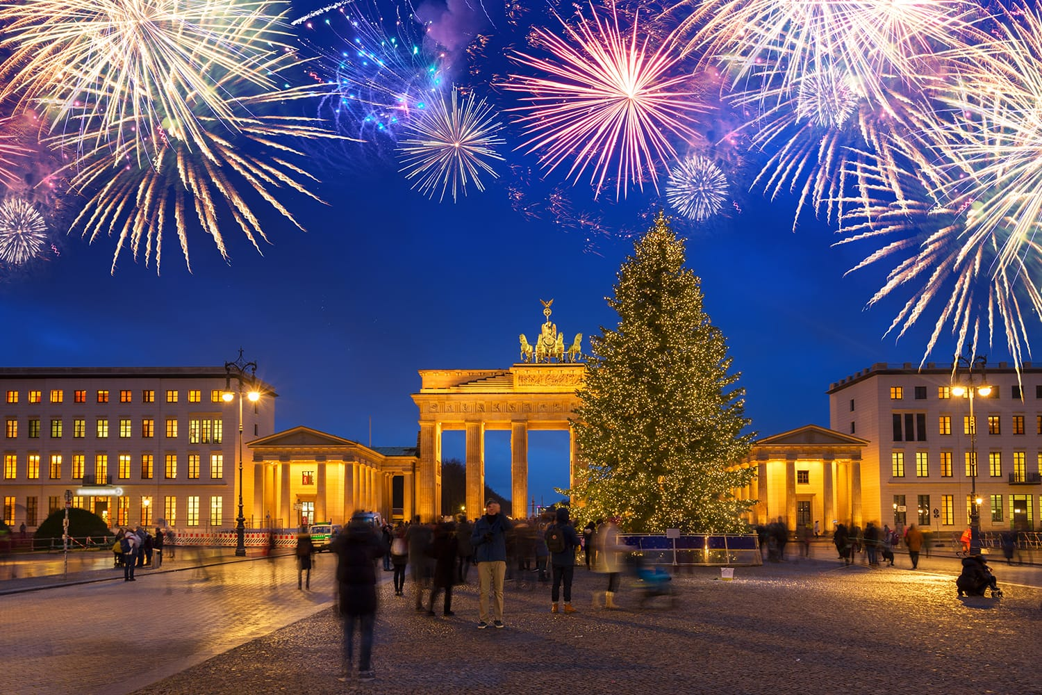 Brandenburg Gate with Christmas tree illuminated at night with fireworks, Berlin Germany
