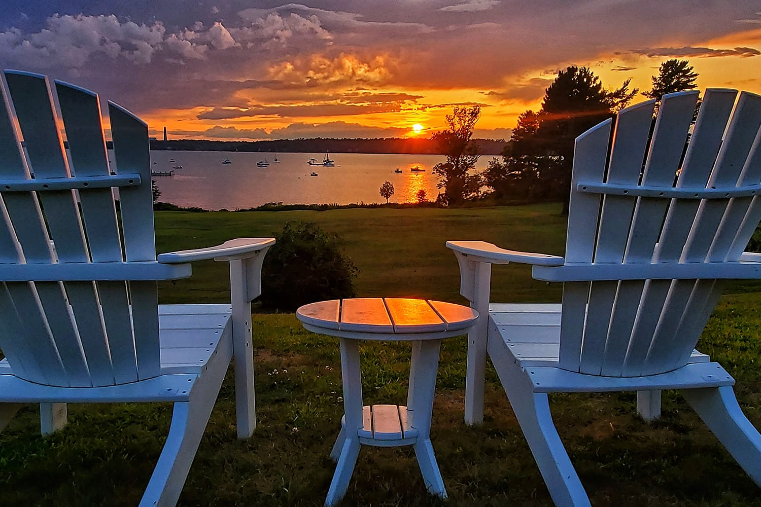 Two empty chairs overlooking a sunset on Chebeague Island, Maine, USA