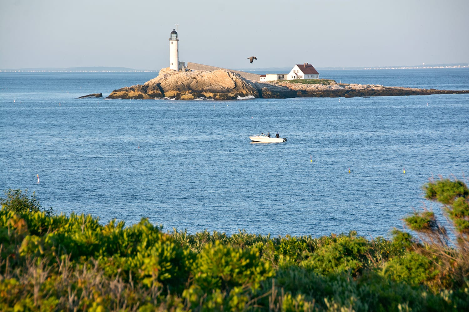 Early morning fishermen try their luck in the strait between Star Island and White Island on a clear summer day. Rye, NH, USA