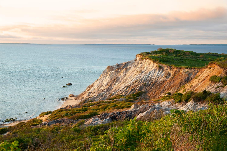 Sun sets illunimating sandy cliffs of Moshup Beach in Aquinnah, on Martha's Vineyard island, in Massachusetts, USA