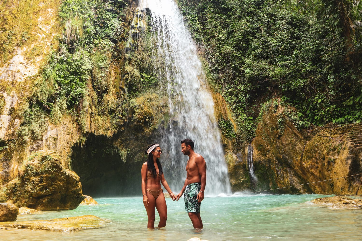 Lovely couple alone in deep forest waterfall from mountain gorge at hidden tropical jungle in Cebu Island in Philippines