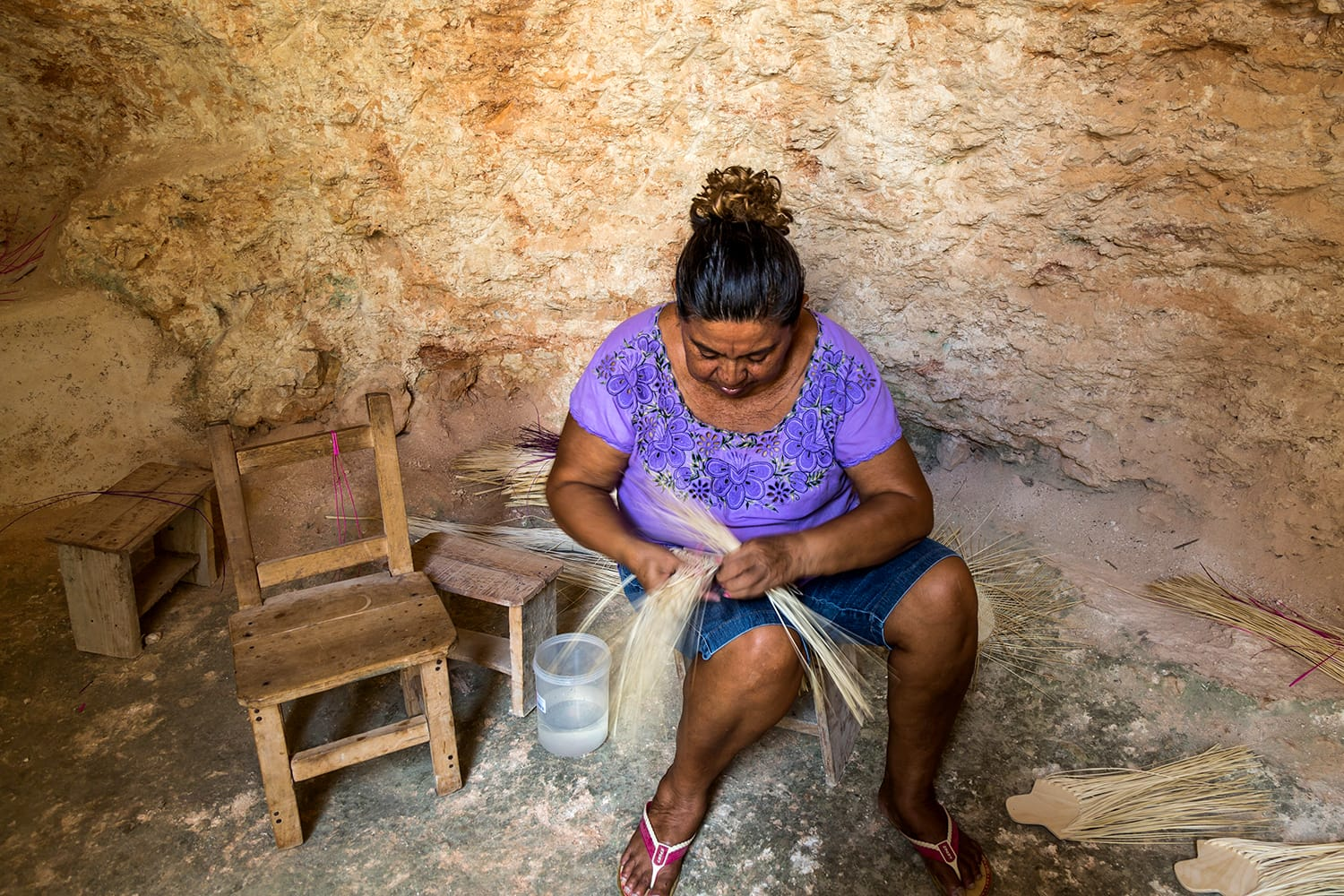 Artisan in cave weaving straw to make a hat in Becal, Mexico