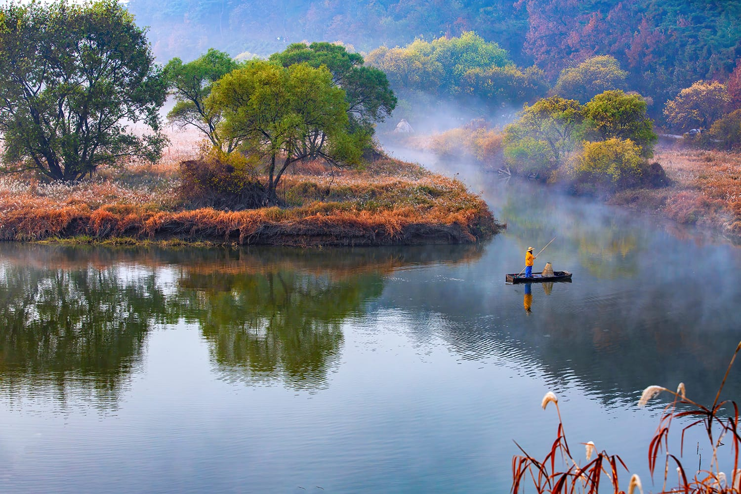A fisherman is standing on boat with bamboo pole at foggy Upo wetland in the morning
