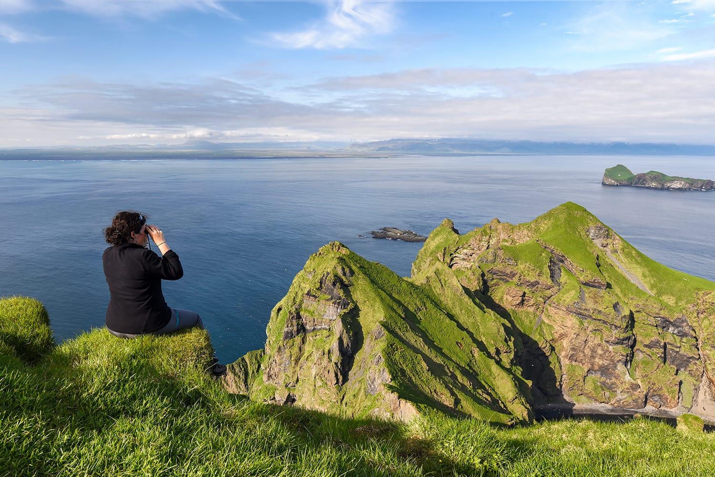 Hiker woman watching the sunset over Heimaey cliffs (Vestmann Islands - south of Iceland)