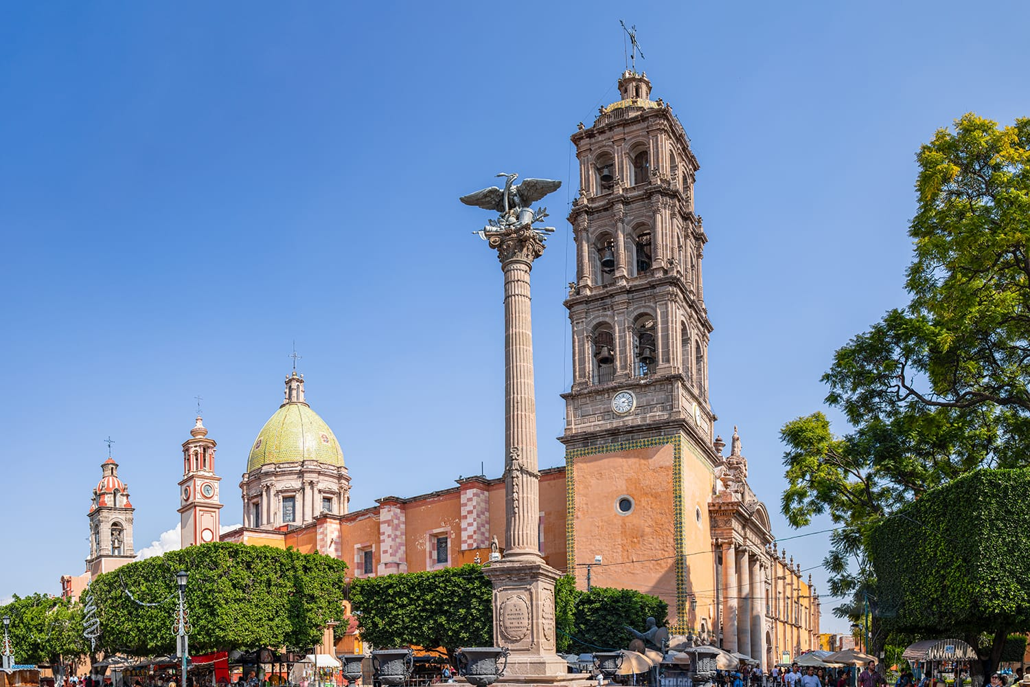 Tourists and locals around the Immaculate Conception Cathedral, with the Independence column at the front in Celaya, Guanajuato, Mexico